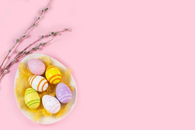 Красочные пасхальные яйца в тарелке в форме яйца с ивовыми веточками на светлом столе