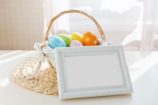 白い木製のテーブルの上の空のフレームとbusketのイースターカラフルな卵。ハッピーイースターテーブル。テキスト用のコピースペース