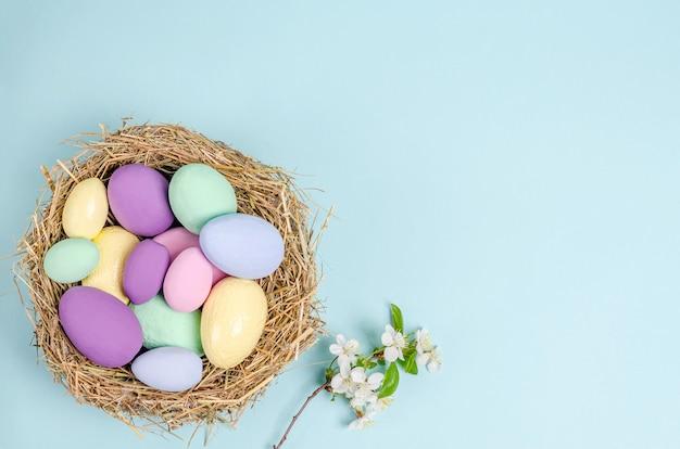 青い背景の上のイースターカラフルな卵。季節性のコンセプト、春、はがき、休日。フラットレイ、コピースペース、テキスト用のスペース。上から見る