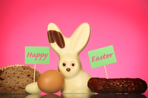 An easter composition of a chocolate bunny, sausage, bread and eggs over pink background