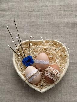 Пасхальная композиция, украшенная кружевом пасхальные яйца в плетеной корзине на льняном фоне. концепция без пластика и без отходов