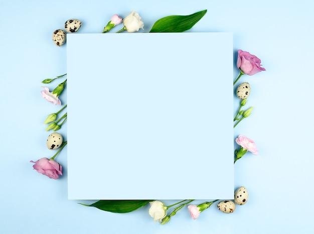 イースター作曲。パステルブルーの背景にイースターの卵、花、紙の空白。フラットレイ、上面図、コピースペース、モックアップ。