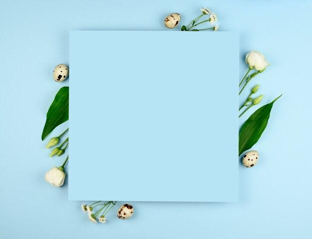 イースター作曲。パステルブルーの背景にイースターの卵、花、紙の空白。白い花。フラットレイ、上面図、コピースペース、モックアップ。