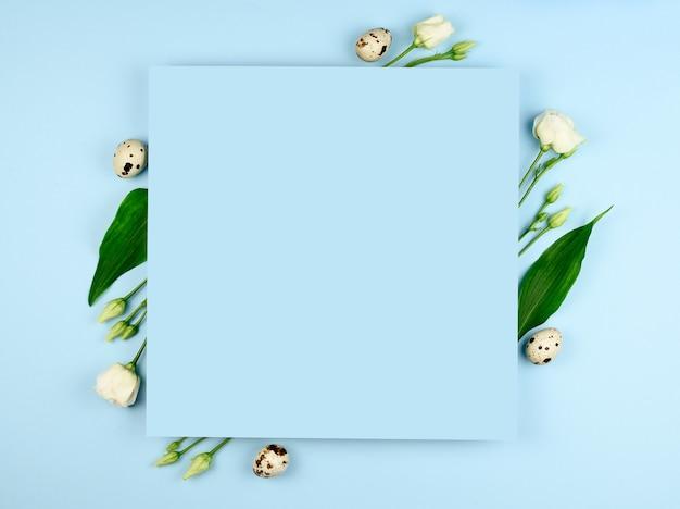 イースター作曲。パステルブルーの背景にイースターの卵、花、紙の空白。白い花。フラットレイ、上面図、コピースペース、モックアップ。 Premium写真