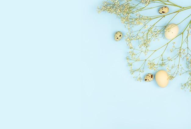 イースター作曲。パステルブルーの背景にイースターの卵、花、紙の空白。