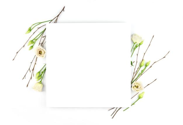 イースター作曲。イースターの卵、花、白い背景の上の紙の空白。白い花。フラットレイ、上面図、コピースペース、モックアップ。