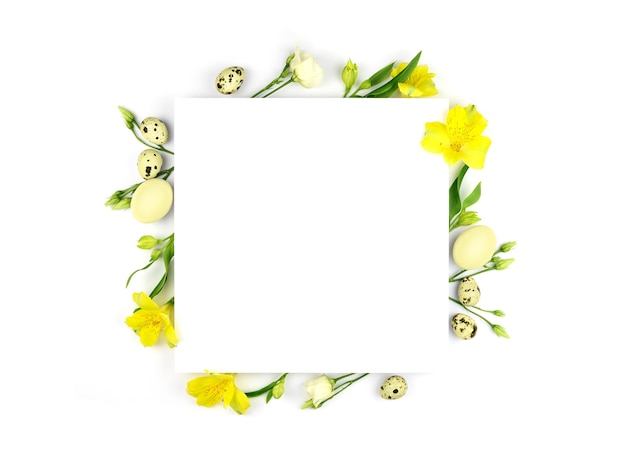 イースター作曲。イースターの卵、花、白い背景の上の紙の空白。黄色い花。フラットレイ、上面図、コピースペース、モックアップ。