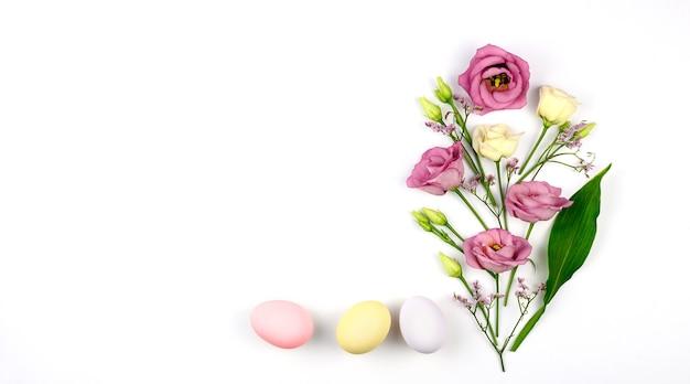 부활절 구성. 부활절 달걀, 꽃, 흰색 바탕에 빈 종이.