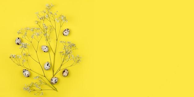 イースター作曲。イースターの卵、花、黄色の背景に空白の紙。