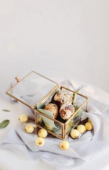 부활절 구성입니다. 실크 리본과 흰색 및 회색 배경에 유리 상자에 부활절 달걀. 공간을 복사합니다.
