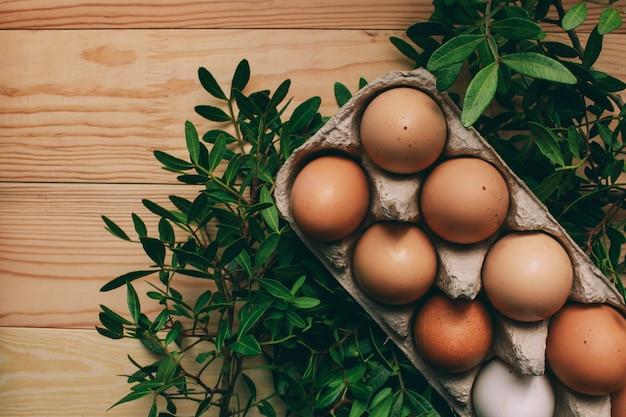 イースターの組成イースターエッグは上から木製の明るい背景イースターコンセプト写真の緑の枝の横にある卵の箱にあります