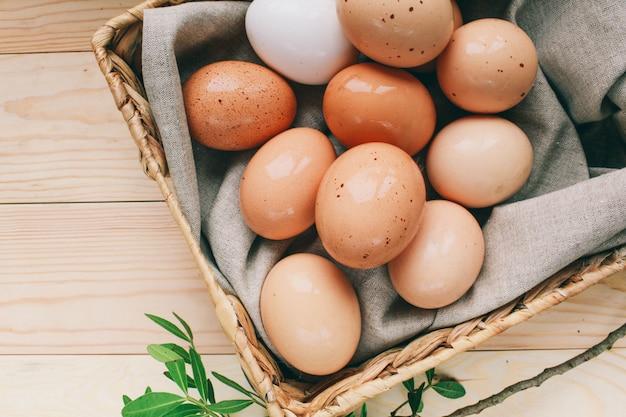 イースターの組成イースターエッグは、上から木製ライトtableeasterコンセプト写真の緑の枝の横にある卵の箱にあります。