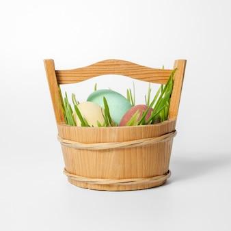 イースターの構成、白い背景の上の緑の草とバスケットの卵。卵は天然染料で塗装されています。