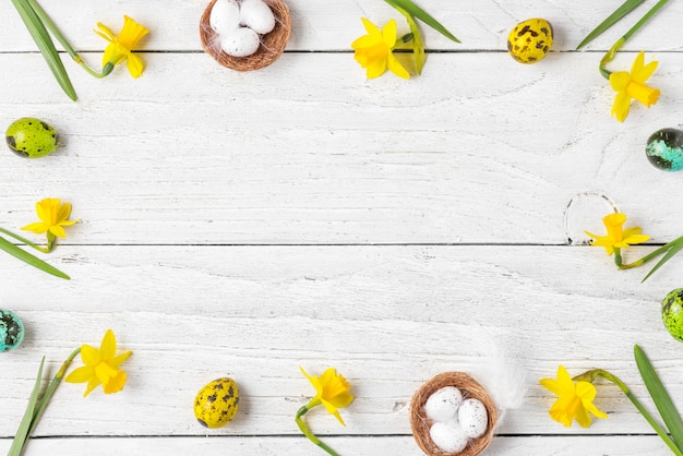 Easter composition. frame made of easter eggs and spring narcissus flowers on white wooden background