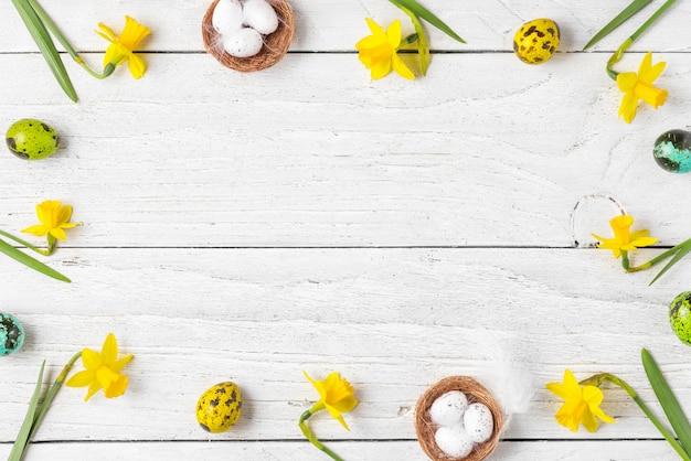 イースターの組成物。イースターエッグと白い木製の背景に春の水仙の花で作られたフレーム
