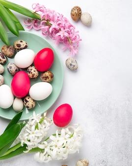 Пасхальная композиция. зеленая тарелка мяты, пасхальные яйца, розовый и белый гиацинт на каменном фоне. скопируйте пространство. вид сверху - изображение