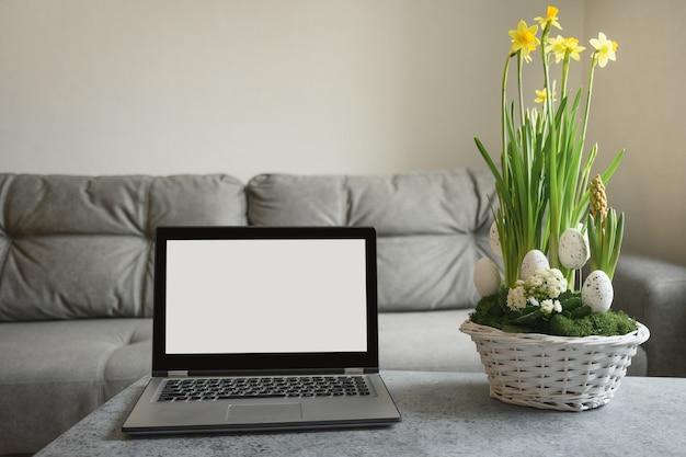 Easter composition and laptop for online translation church service in quarantine time. spring interior for online diy workshop.