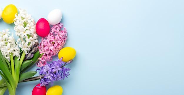 Пасхальная композиция. разноцветные пасхальные яйца и гиацинты на синем фоне. концепция пасхи. копировать пространство - изображение