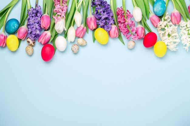 Easter composition. multicolored easter eggs, tulips and hyacinths on blue background. easter concept. copy space