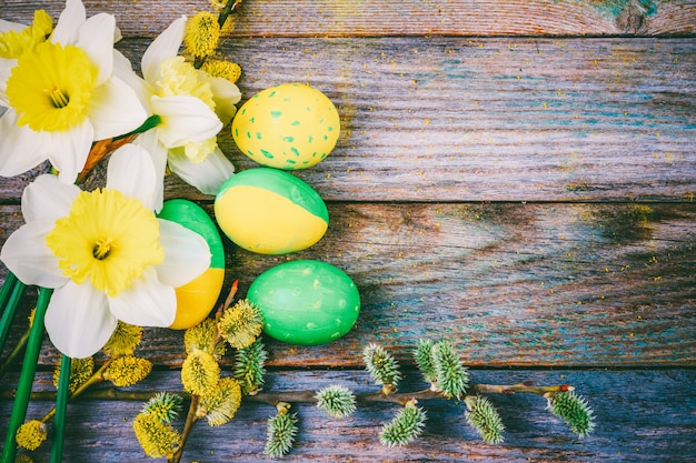 Easter composition of narcissus flower blooming willow twigs and easter eggs with a pattern of yellow and green color on a wooden retro background with copy space close-up top view