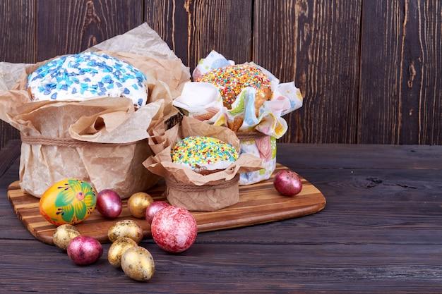 カップケーキと卵のイースター構成。素朴な木製の背景。