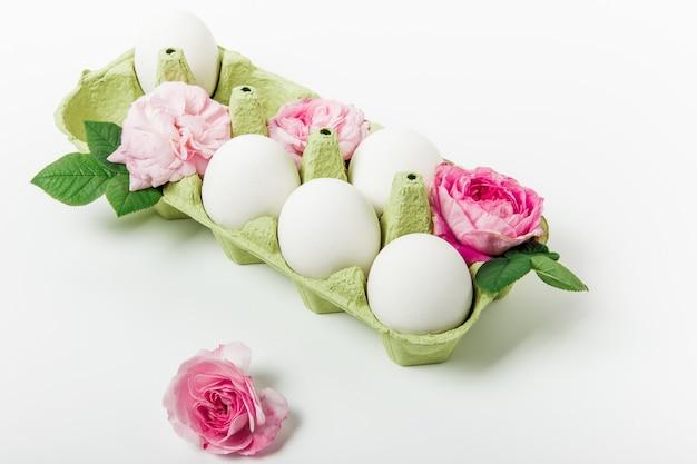 卵とピンクの花のイースター構成。白色の背景。イースターと休日のコンセプト。ミニマリストスタイル