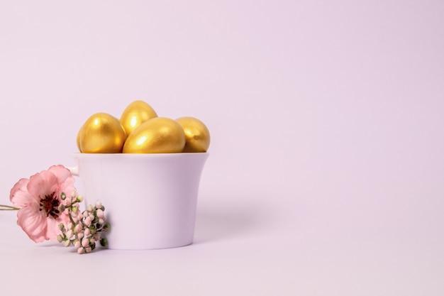 도자기 컵에 황금 장식 달걀과 분홍색 꽃의 부활절 구성
