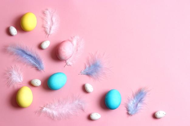 컬러 배경에 페인트 계란과 깃털의 부활절 구성