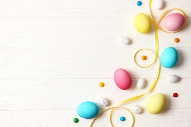 Easter composition of painted eggs and feathers on a colored background. easter background. high quality photo