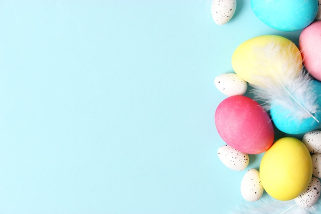 Easter composition of painted eggs and feathers on a colored background