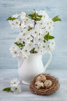 Easter composition of quail eggs with the bouquet of blossom cherry