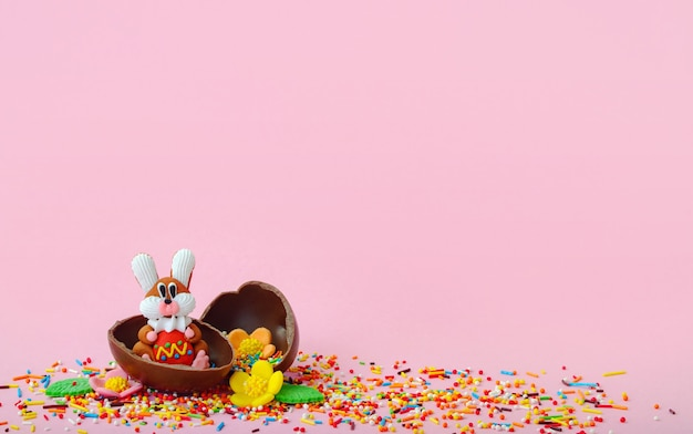 Easter composition. sweet flowers, sweet bunny and chocolate eggs in foil on pink background with empty place for inspiration.