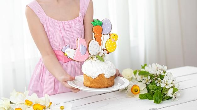 棒にジンジャーブレッドで飾られたお祝いのケーキとイースターの構成。イースター休暇の準備の概念。