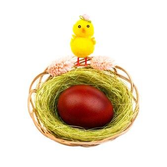 白い背景で隔離の巣に黄色い鶏と暗赤色の卵とイースターの構成