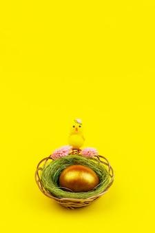 コピースペースと黄色の背景の上の巣に黄色い鶏と金色の卵とイースターの構成