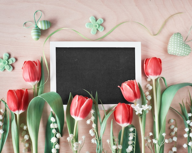 Easter composition with blackboard framed with spring flowers, tulips and lily of the valley, text
