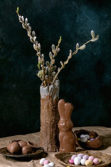 Easter composition with blossom willow branches in ceramic vase, traditional chocolate rabbit, eggs and sweets on table with crumpled craft paper