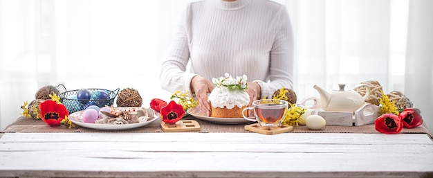 Easter composition with cake in female hands, tea, flowers, eggs and decor details. easter family holiday concept.