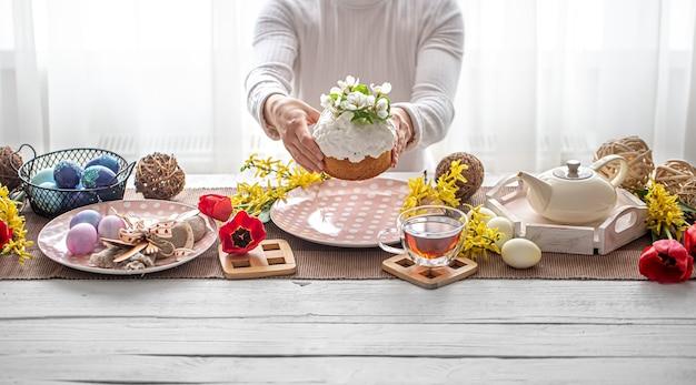 여성 손, 차, 꽃, 계란 및 장식 세부 사항에 케이크와 함께 부활절 구성. 부활절 가족 휴가 개념.