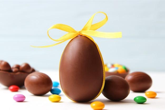 木製の背景にチョコレートの卵とチョコレートのウサギとイースターの構成