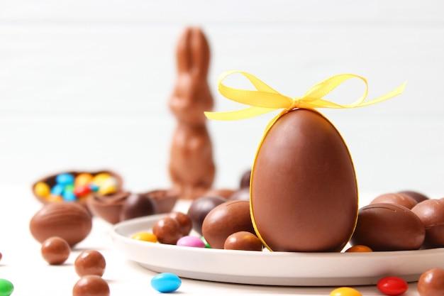 Пасхальная композиция с шоколадными яйцами и шоколадным кроликом на деревянном фоне