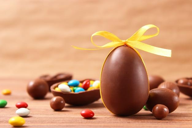 나무 배경에 초콜릿 달걀과 초콜릿 토끼가 있는 부활절 구성 프리미엄 사진
