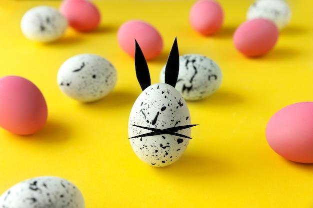 着色された卵とウサギの耳と黄色の背景に顔と卵のイースター組成