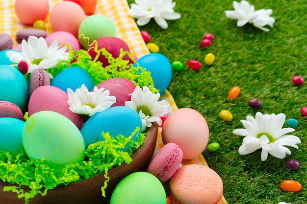 Easter composition with colored eggs and bright candies on yellow tablecloth