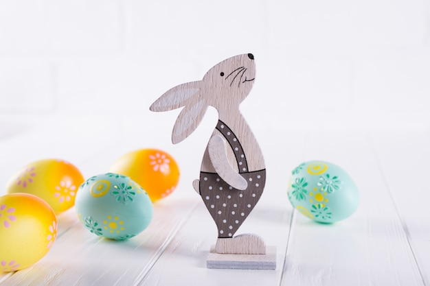 Easter composition with colorful easter eggs, decorative wooden bunny. template for lettering