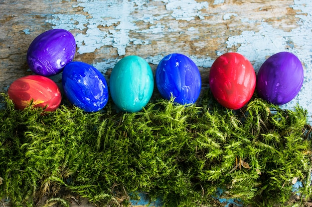 Easter composition with colorful easter eggs on moss in vintage tray. top view.