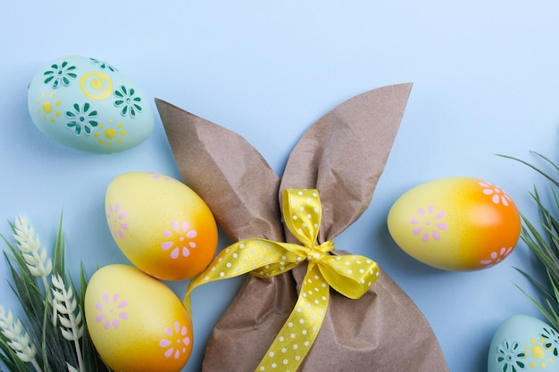 Easter composition with craft paper package in the shape of bunny, colorful easter eggs, and flowers. flat lay, top view,