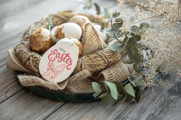 Easter composition with decorated easter eggs and decorative nest on a wooden surface