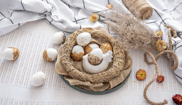 Пасхальная композиция с украшенными пасхальными яйцами в гнезде среди цветов