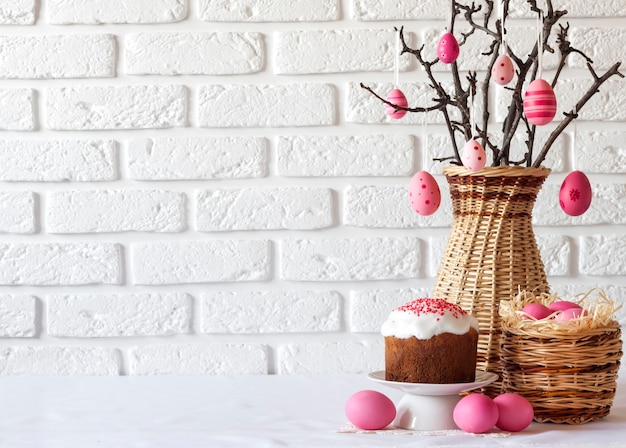 籐の花瓶に飾られた木の枝、籐のバスケットにピンク色の卵、白い背景にイースターケーキのイースター構成。コピースペース